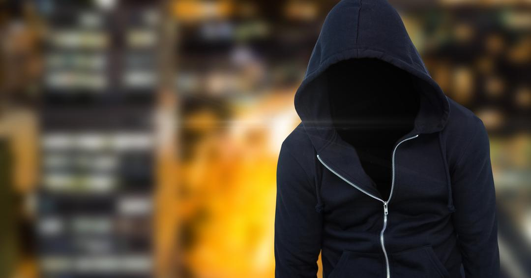 Digital composite of Anonymous criminal man wearing hood in front of city lights