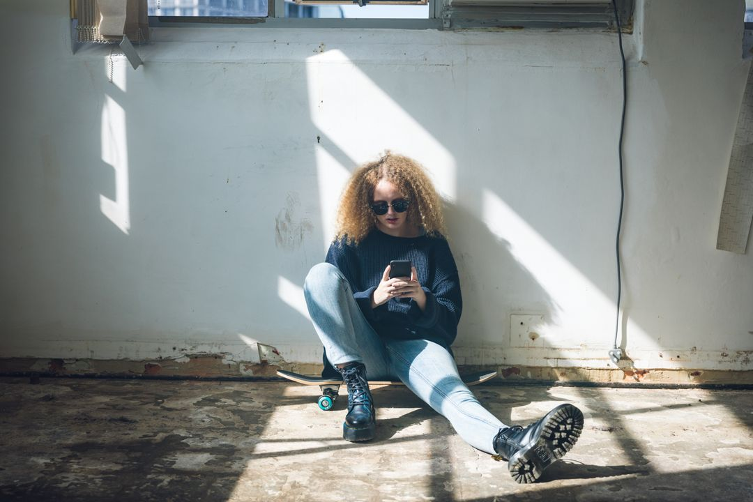 Front view of a hip young Caucasian woman in an empty warehouse, sitting on the floor, wearing sunglasses, holding and using her smartphone. Free Stock Images from PikWizard