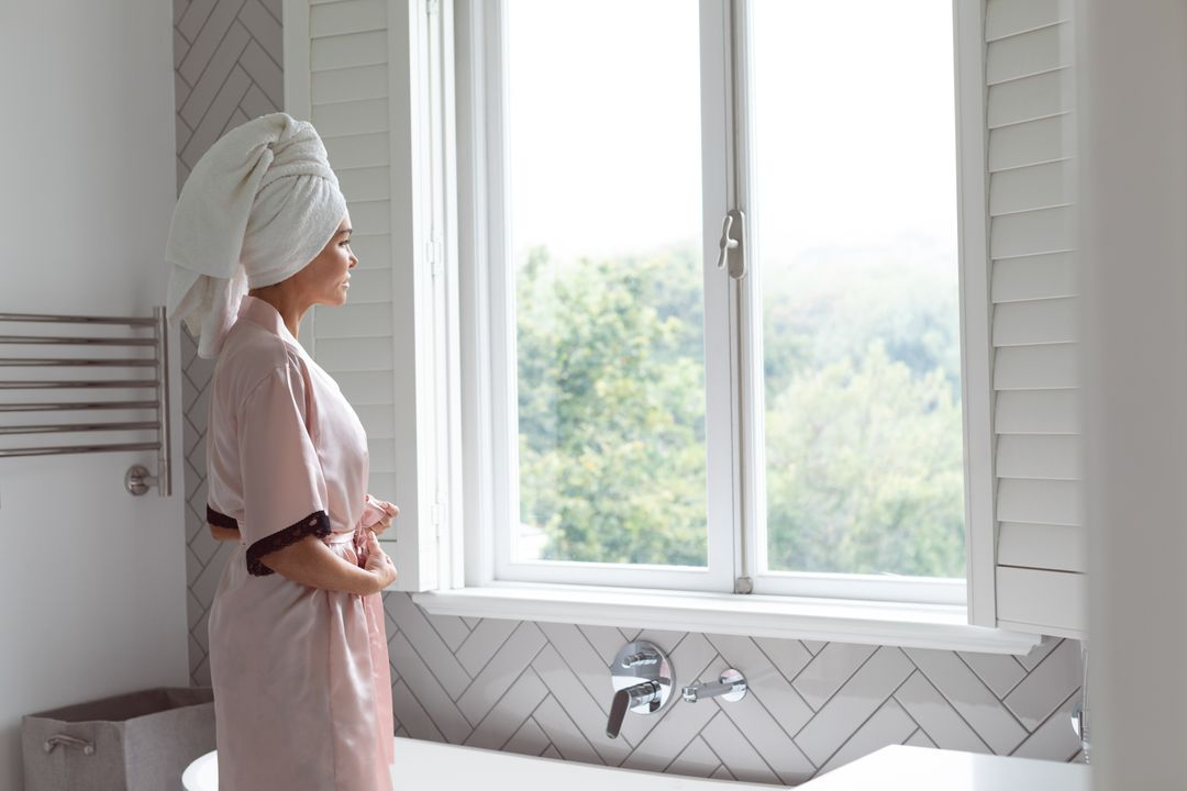 Side view of woman looking outside the window while tying knot of nightwear in bathroom at home