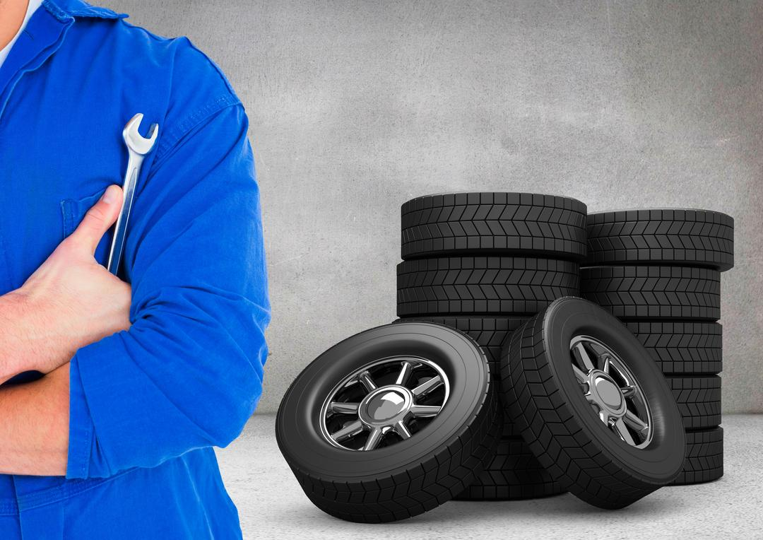 Digital composite image of mechanic holding lug wrench with tyres in background