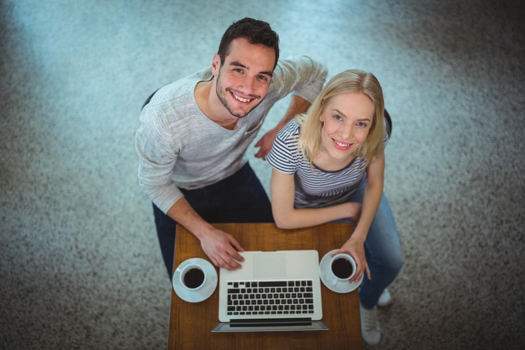 Portrait of smiling couple using laptop while having black coffee in café