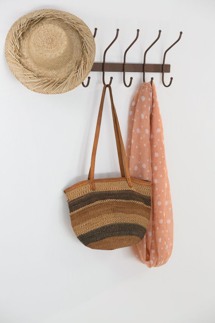 Hat, bag and scarf hanging on hook against white wall