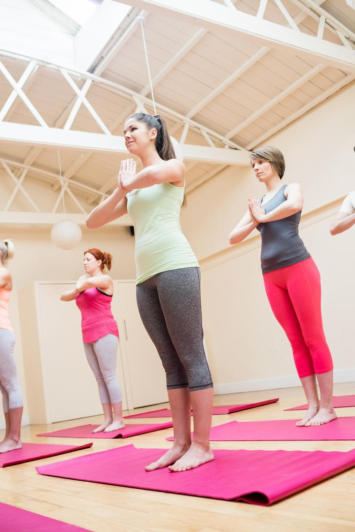 Group of people performing tree-pose yoga exercise in the fitness studio Free Stock Images from PikWizard