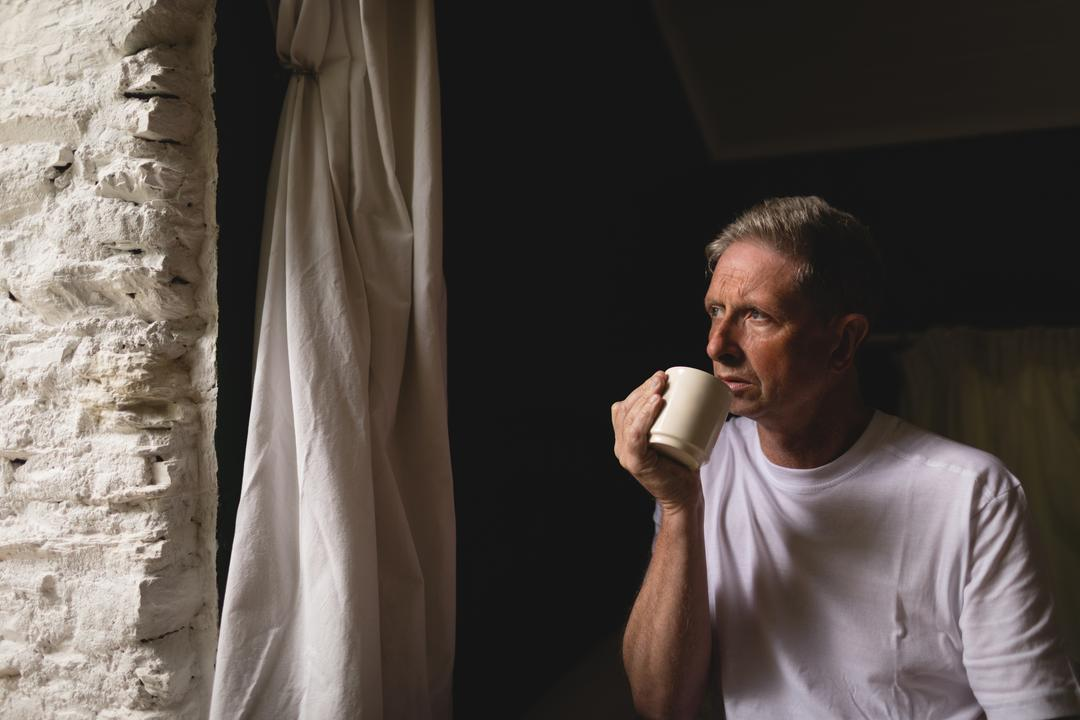 Thoughtful senior man having coffee near window at home