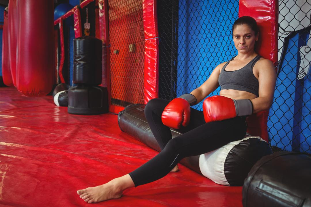 Portrait of female boxer sitting on punching bag in fitness studio