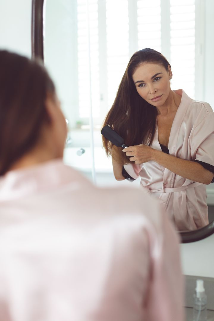 Reflection of woman in mirror combing hair in bathroom at home