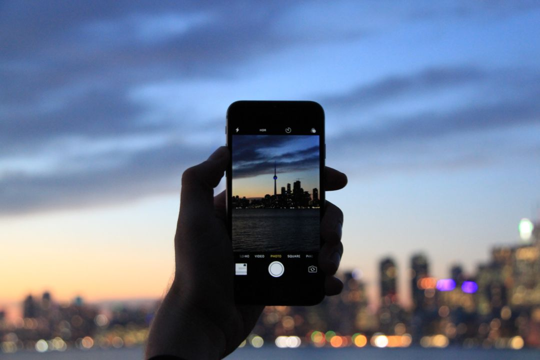 A blogger taking a picture of a city at night on their phone