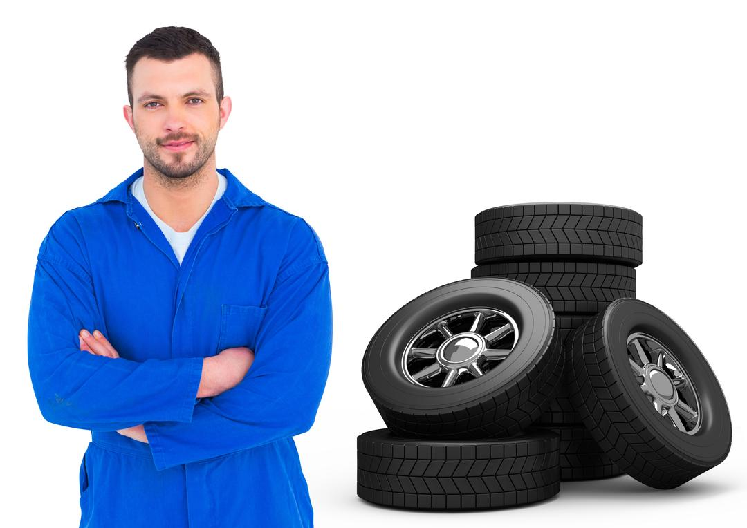 Portrait of car mechanic standing with arms crossed and tyres on white background Free Stock Images from PikWizard