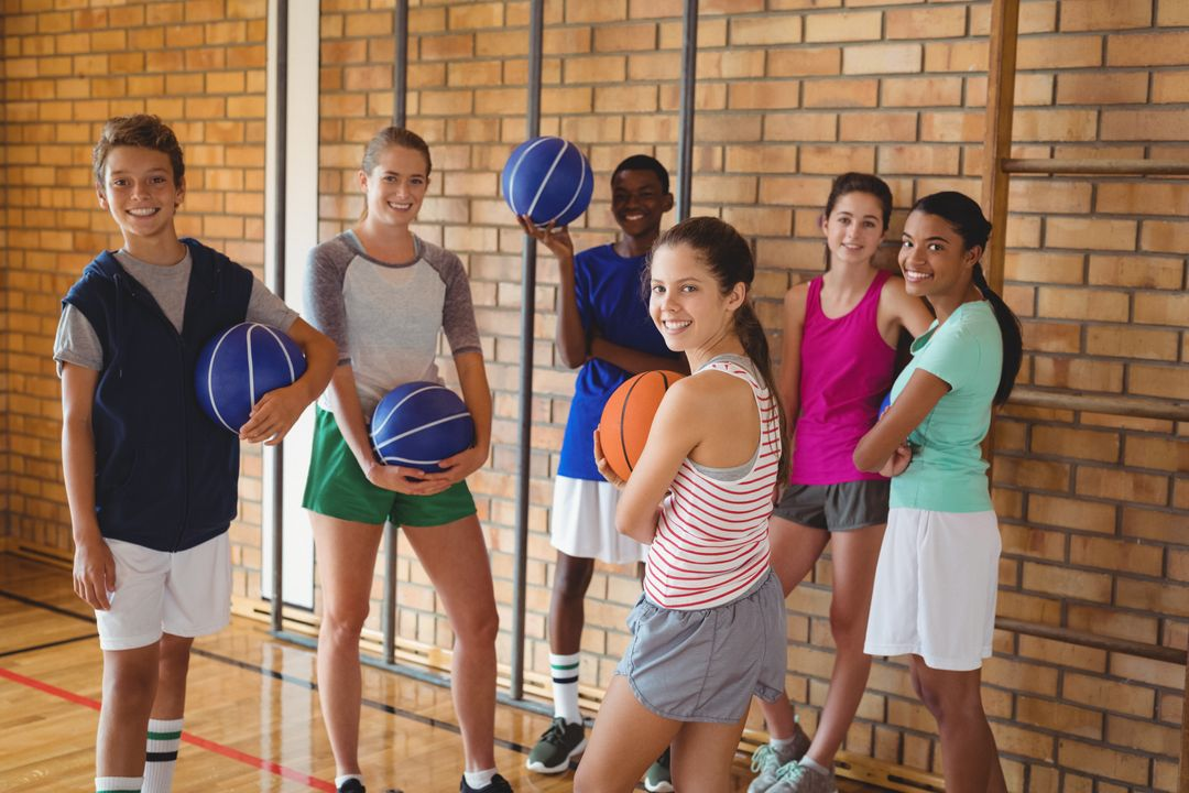 Portrait of happy high school kids standing with basketball in the court Free Stock Images from PikWizard