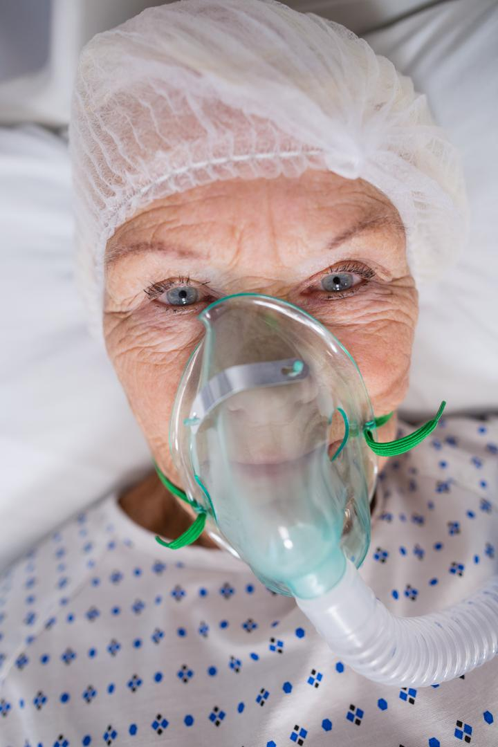 Close-up of senior patient wearing oxygen mask lying on hospital bed