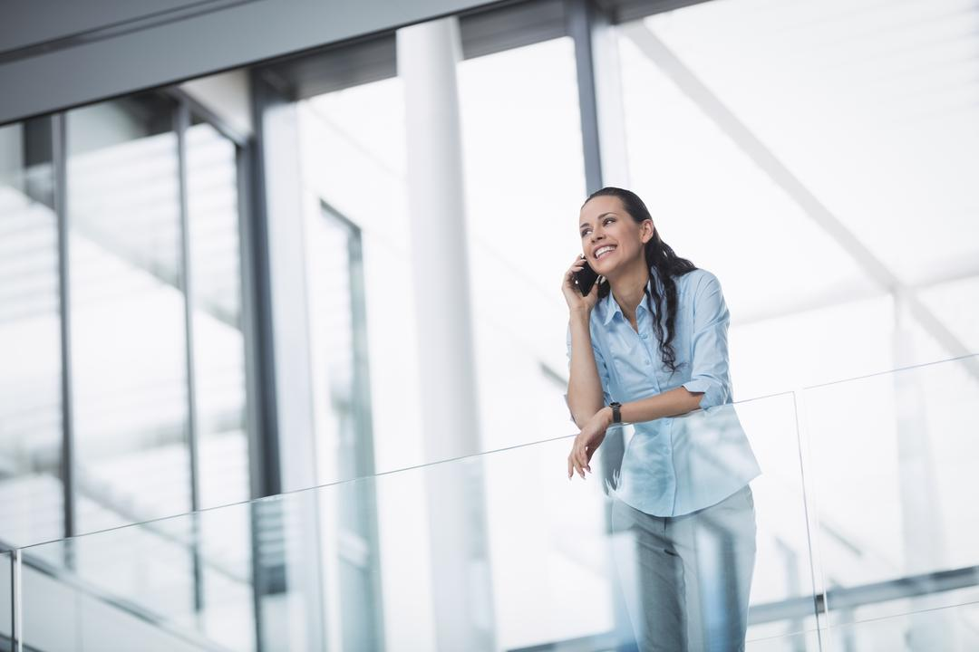 Businesswoman talking on mobile phone inside office building