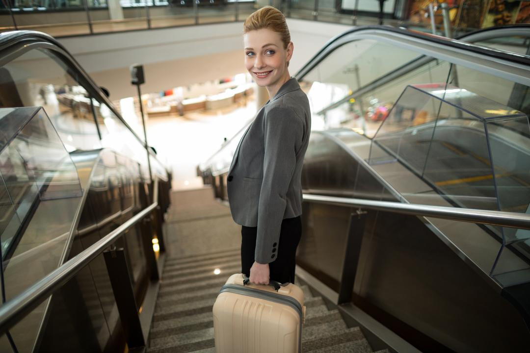 Business woman standing on escalator with luggage at airport