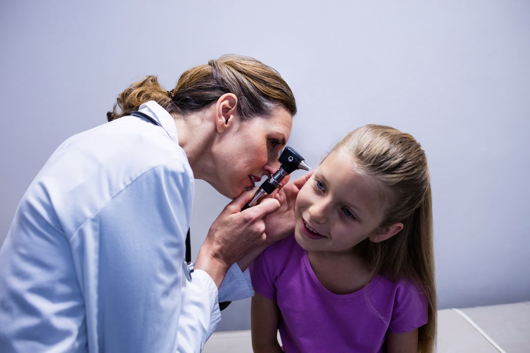 Female doctor examining patient ear with otoscope in hospital Free Stock Images from PikWizard