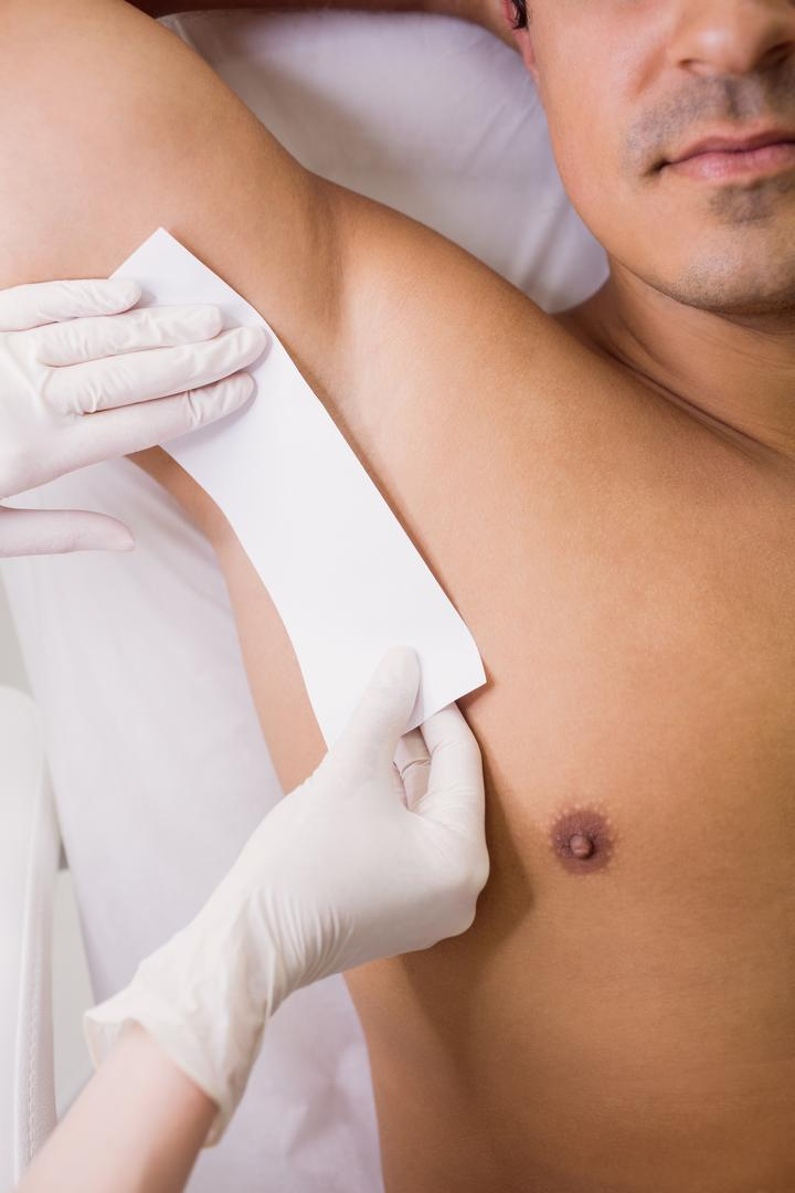 Close up of doctor waxing male patient skin in clinic Free Stock Images from PikWizard