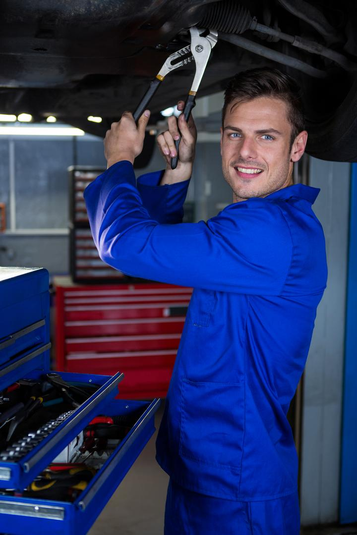 Portrait of happy mechanic servicing a car at repair garage