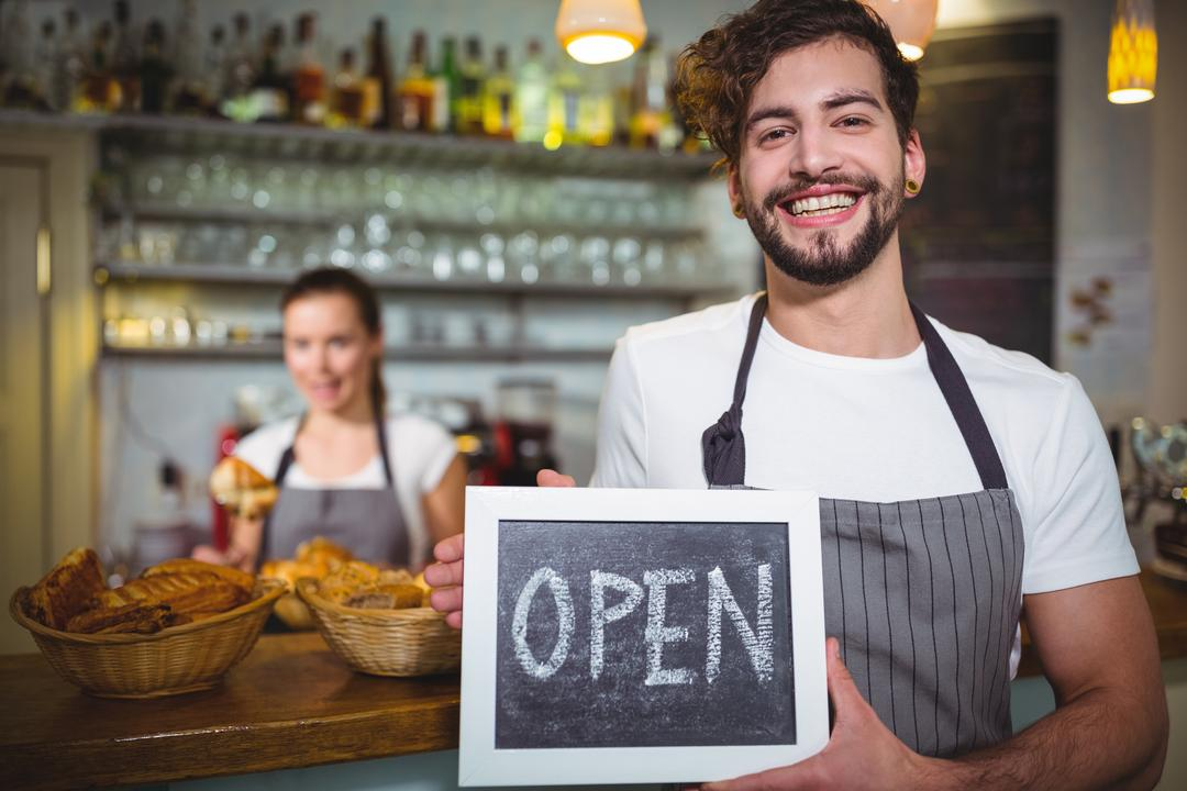 Portrait of smiling waiter showing slate with open sign in café