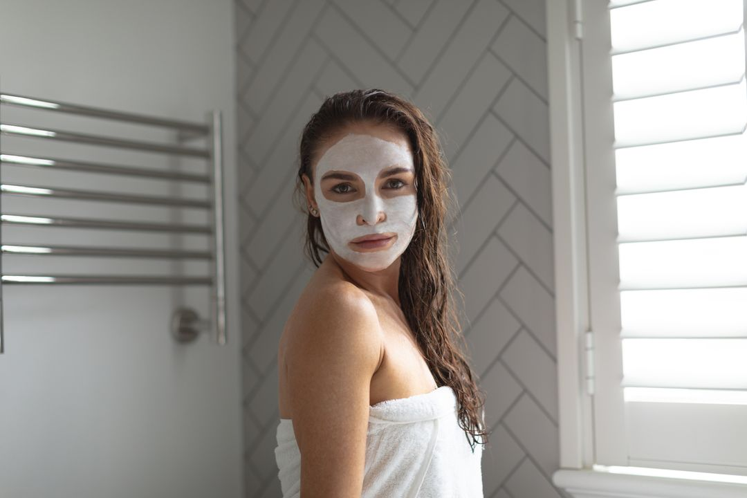 Portrait of woman with facial mask standing in bathroom at home Free Stock Images from PikWizard