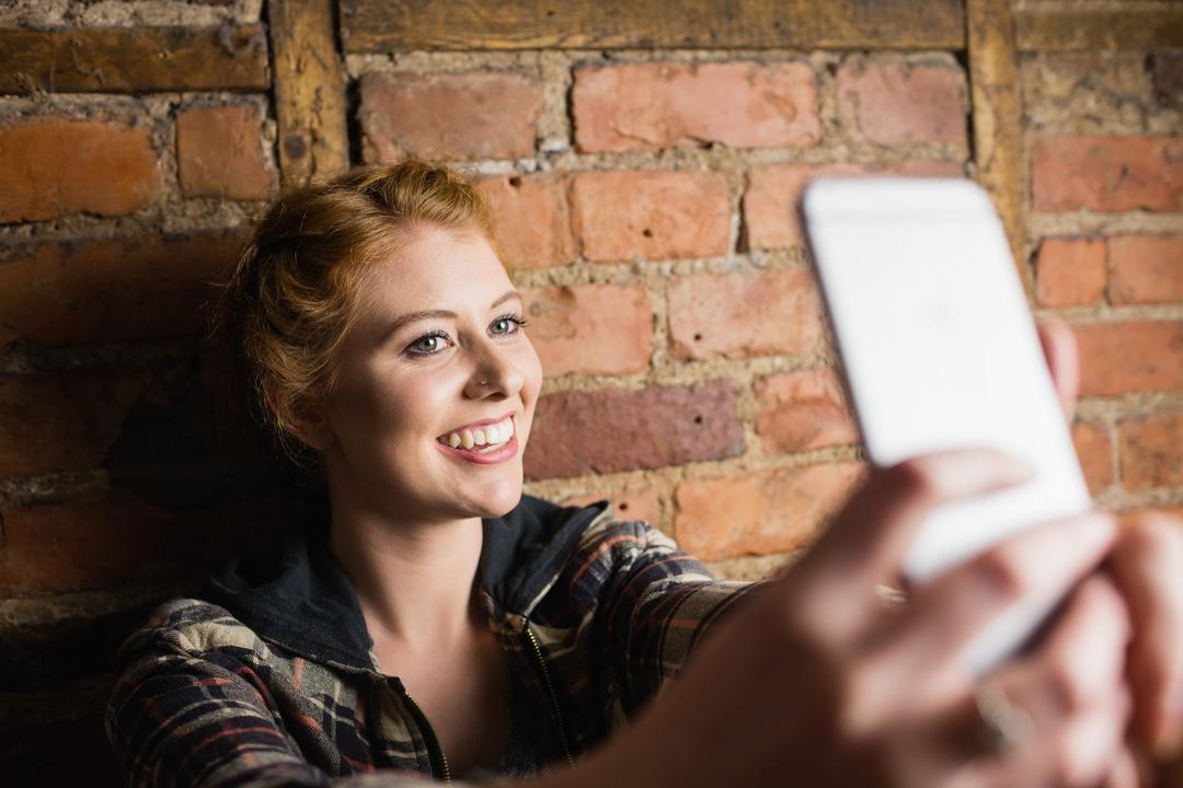 Woman standing against brick wall and taking a selfie on her mobile phone