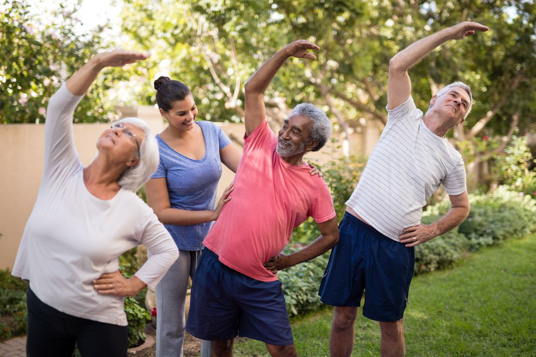 Trainer assisting senior people while exercising at park