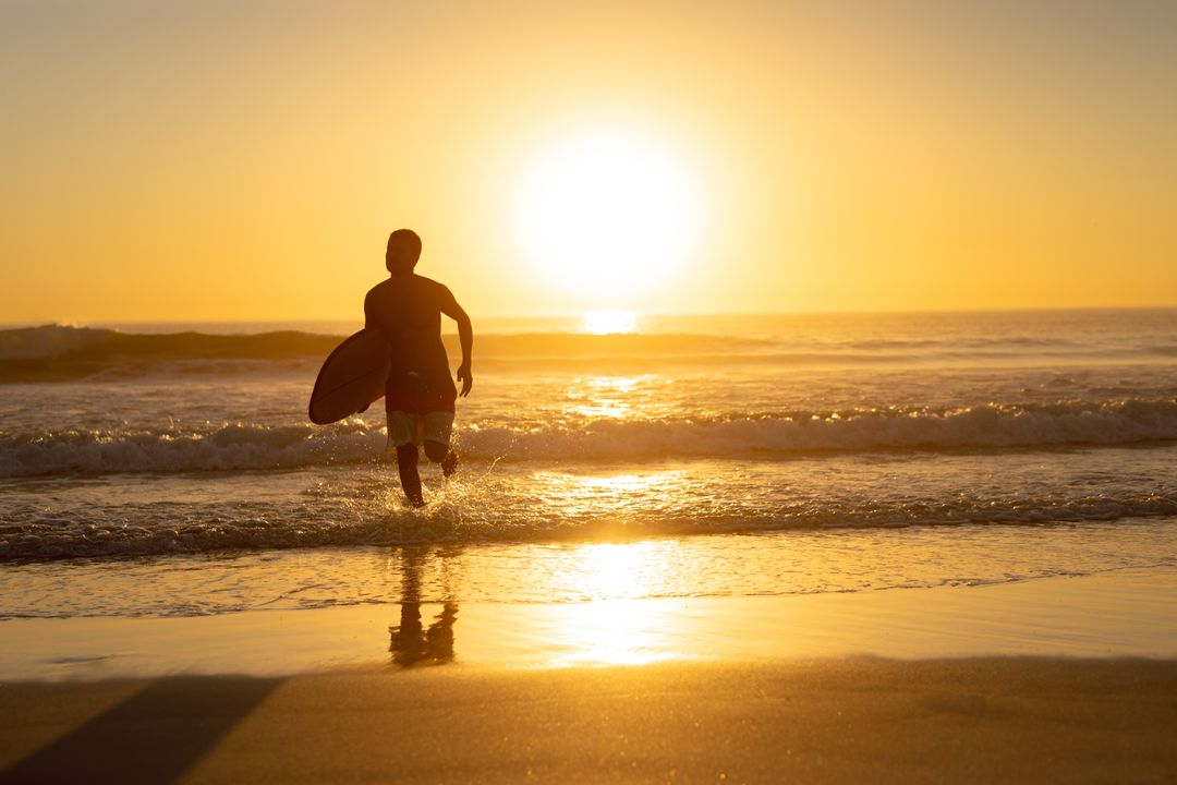 Man running with surfboard on the beach during sunset