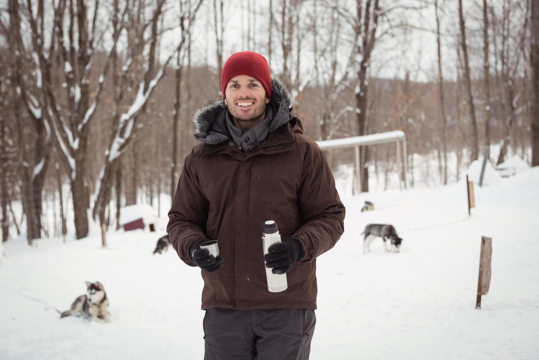Musher holding thermos during winter
