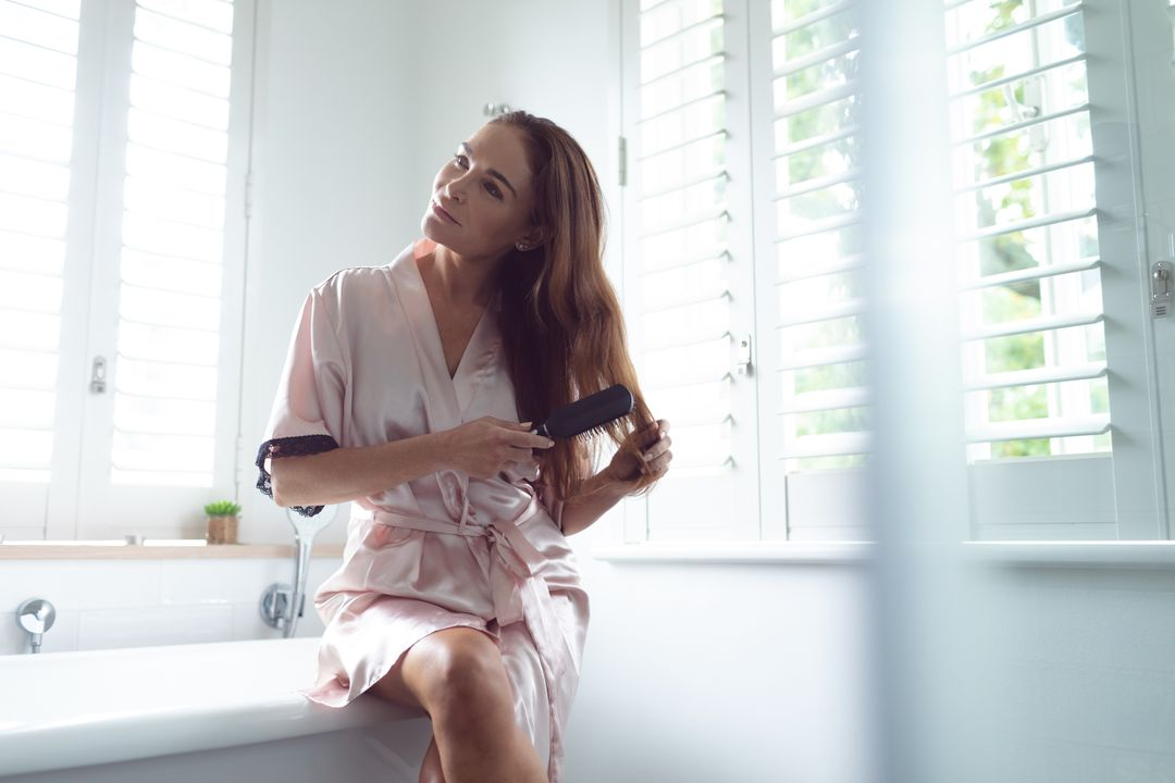 Woman combing her hair while sitting on the edge of bathtub in bathroom at home