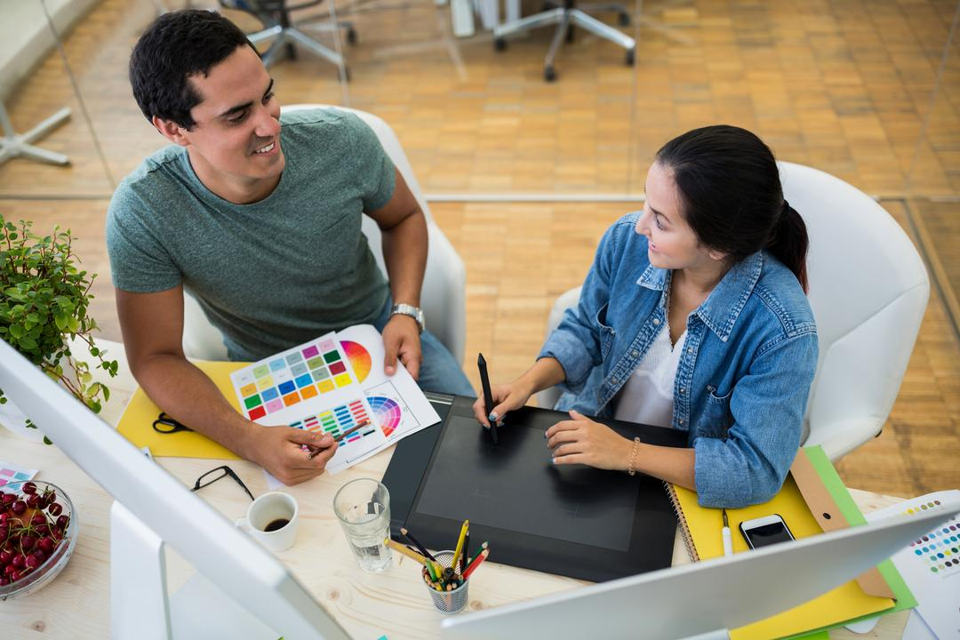 Male and female graphic designers interacting with each other in office