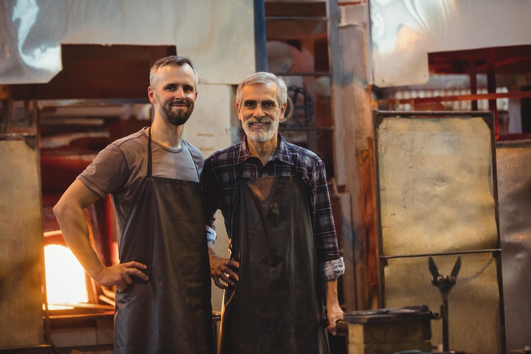 Portrait of team of glassblowers with arms crossed at glassblowing factory Free Stock Images from PikWizard
