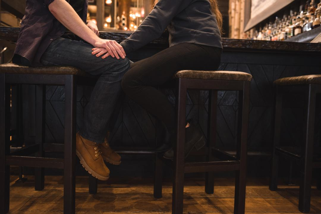 Low section of romantic couple sitting on stool at bar counter Free Stock Images from PikWizard