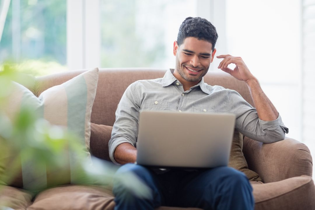 Man sitting on sofa and using laptop in living room at home Free Stock Images from PikWizard