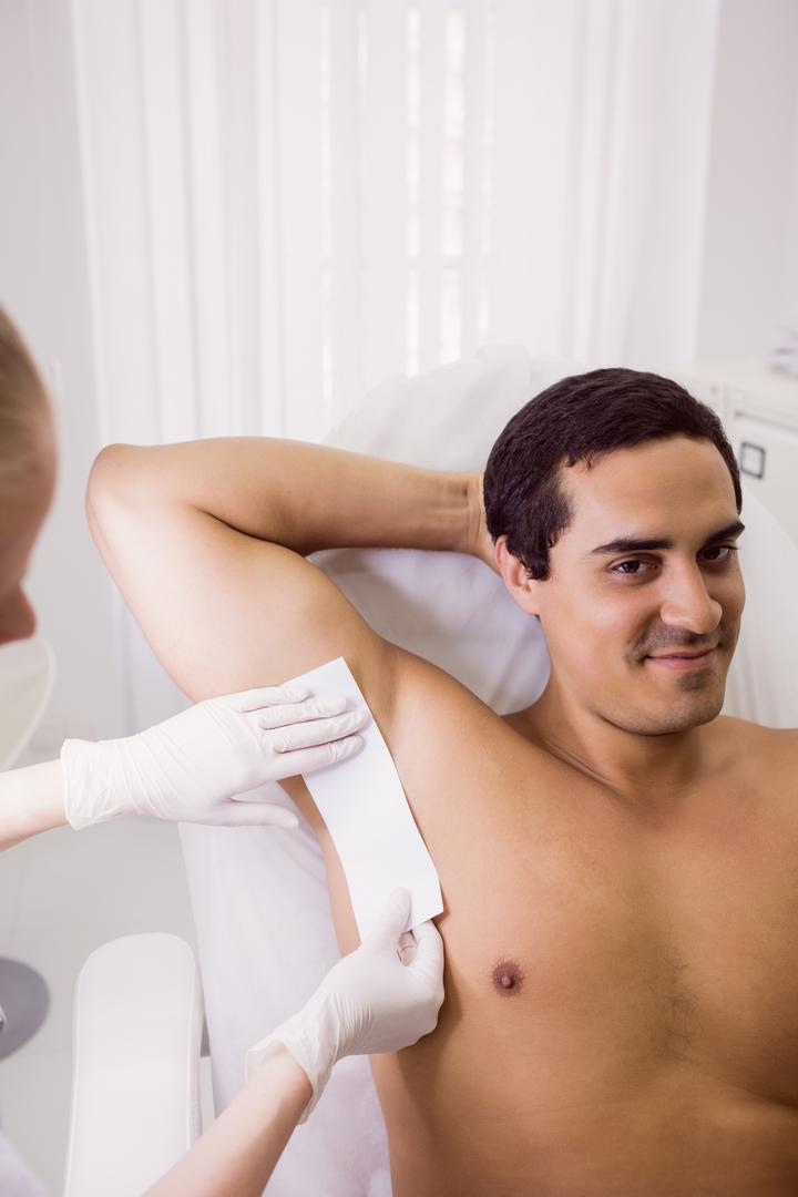 Doctor waxing male patient skin in clinic Free Stock Images from PikWizard