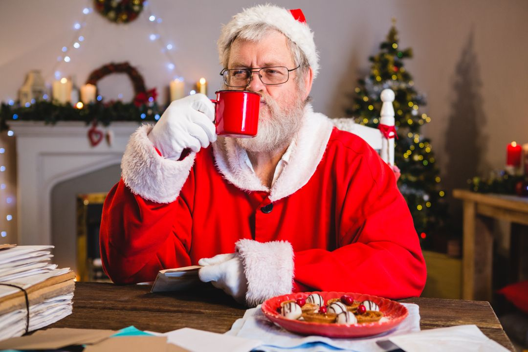 Santa Claus having coffee while holding a letter at home Free Stock Images from PikWizard