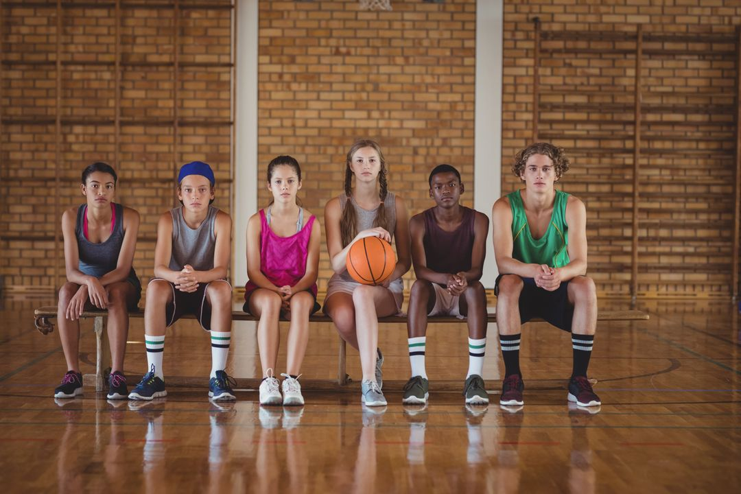 Portrait of high school kids sitting on a bench in basketball court Free Stock Images from PikWizard