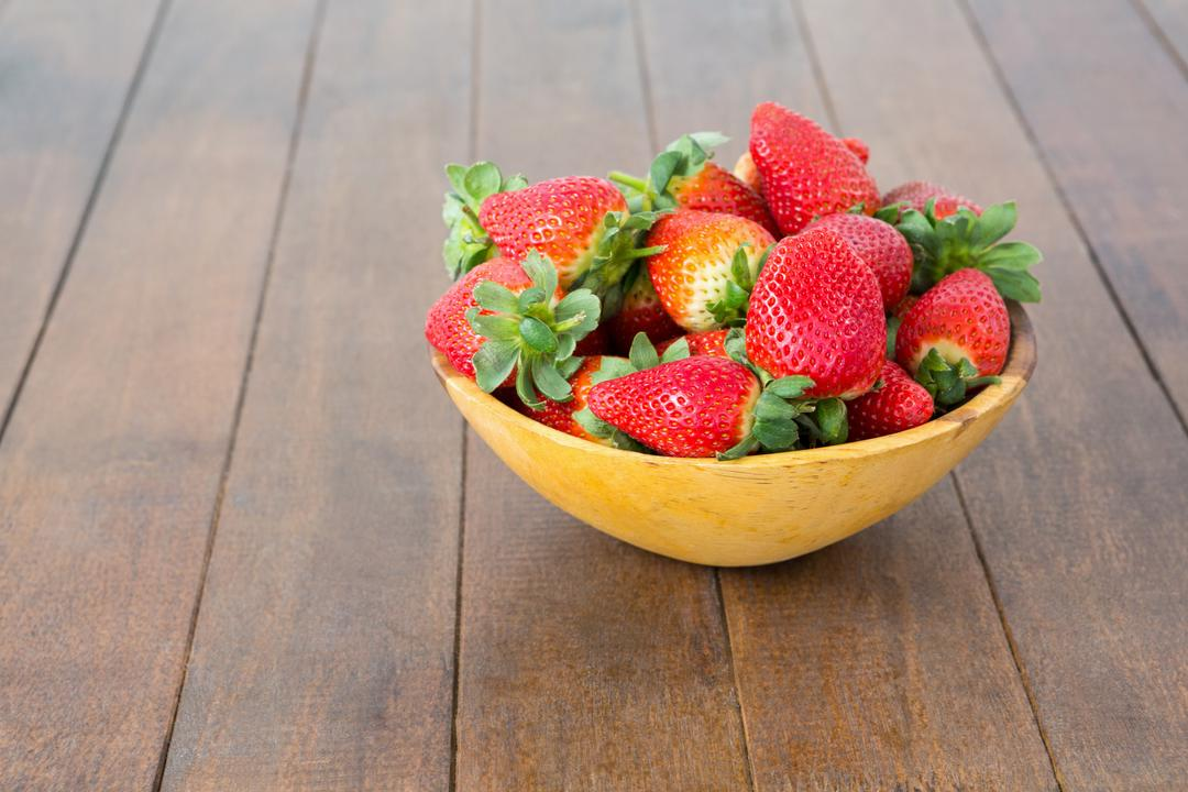 Bowl of fresh strawberries on wooden board