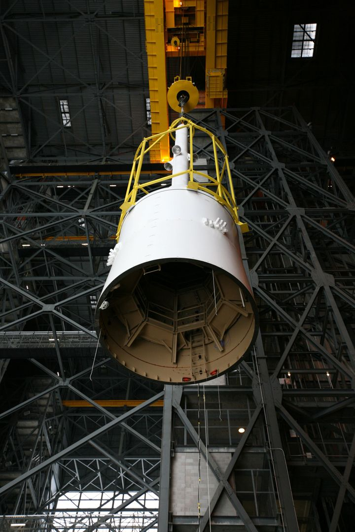 "CAPE CANAVERAL, Fla. – In the Vehicle Assembly Building's transfer aisle, assembly of the Ares I-X rocket nears completion. The yellow framework, nicknamed the ""birdcage,"" moves Super Stack 5 from High Bay 4 over the transfer aisle. The stack will be positioned on top of the segments already in place on the mobile launcher platform in High Bay 3, completing assembly of the 327-foot-tall rocket.  Five super stacks make up the rocket's upper stage that is integrated with the four-segment solid rocket booster first stage. Ares I-X is the test vehicle for the Ares I, which is part of the Constellation Program to return men to the moon and beyond. The Ares I-X flight test is targeted for Oct. 31, pending formal NASA Headquarters approval. Photo credit: NASA/Dimitri Gerondidakis"