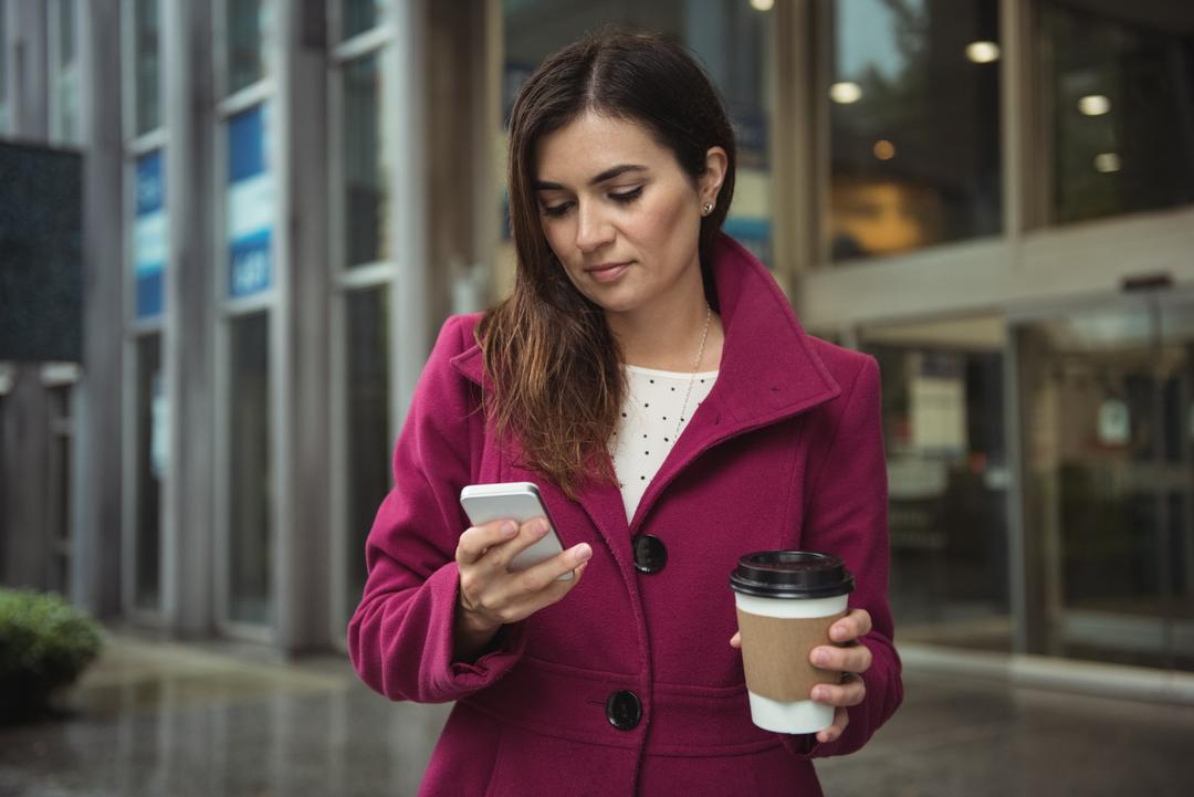 Businesswoman holding disposable coffee cup and using mobile phone on street