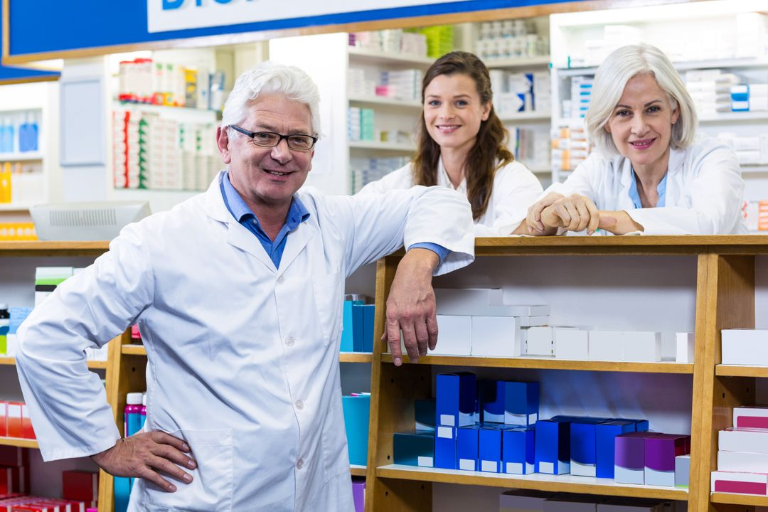 Portrait of smiling pharmacists standing at counter in pharmacy Free Stock Images from PikWizard