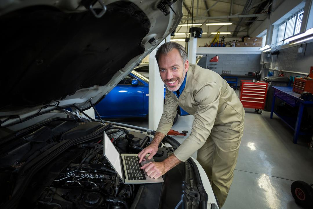 Portrait of smiling mechanic using laptop while servicing a car engine in repair shop