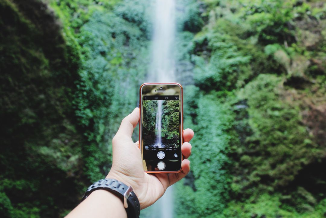 Man taking a picture of a waterfall on his smartphone