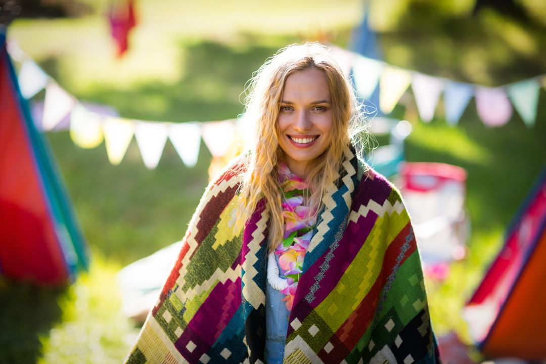 Portrait of woman wrapped in blanket in park on a sunny day Free Stock Images from PikWizard