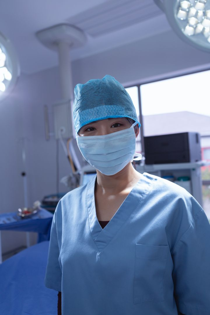 Front view of female surgeon with surgical mask looking at camera in operation room at hospital