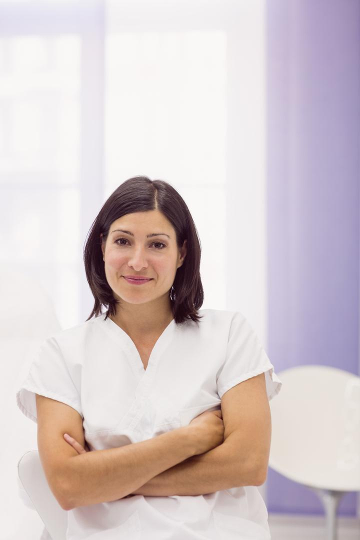 Portrait of female dermatologist standing with arms crossed in clinic