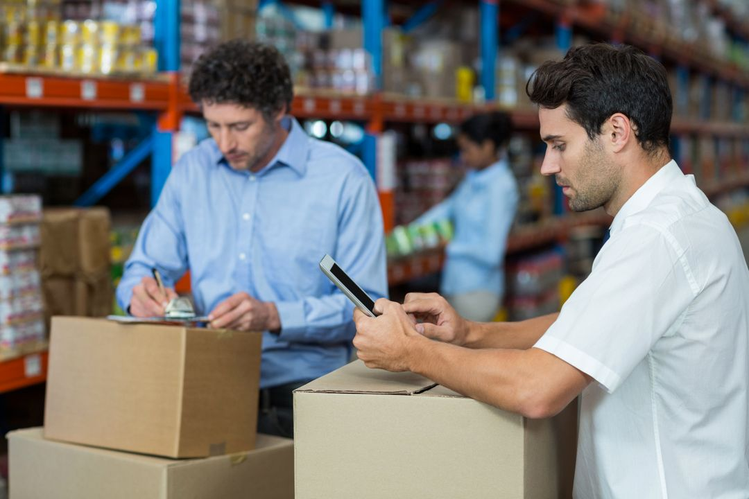 Two workers leaning on boxes in a warehouse with one looking at tablet and one writing on clipboard