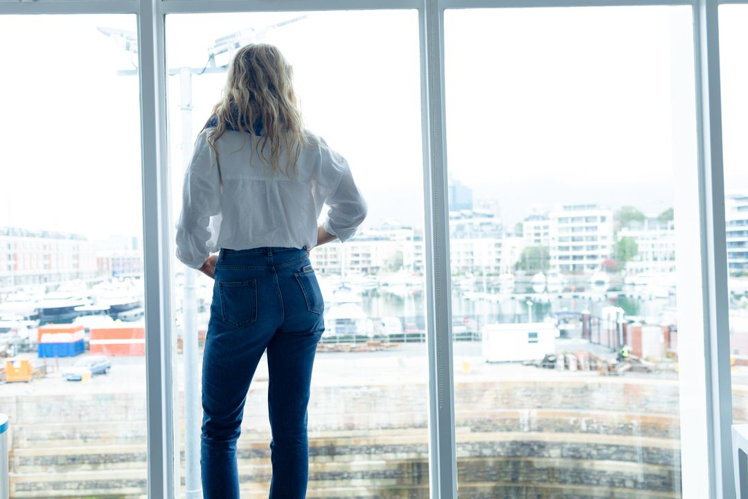 Rear view of young Caucasian businesswoman standing near window in a modern office