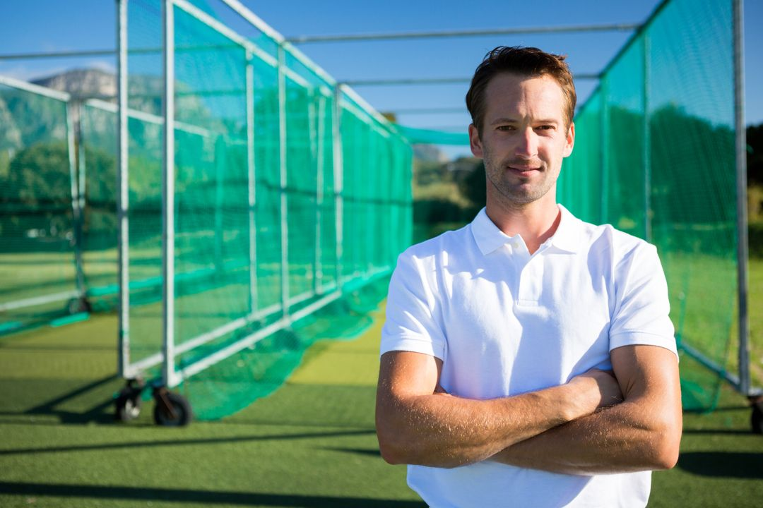 Portrait of young cricketer standing with arms crossed against net on field Free Stock Images from PikWizard