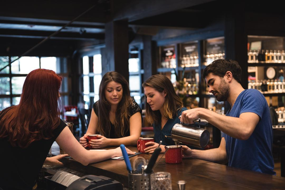 Friends holding coffee at bar counter and interacting with bartender