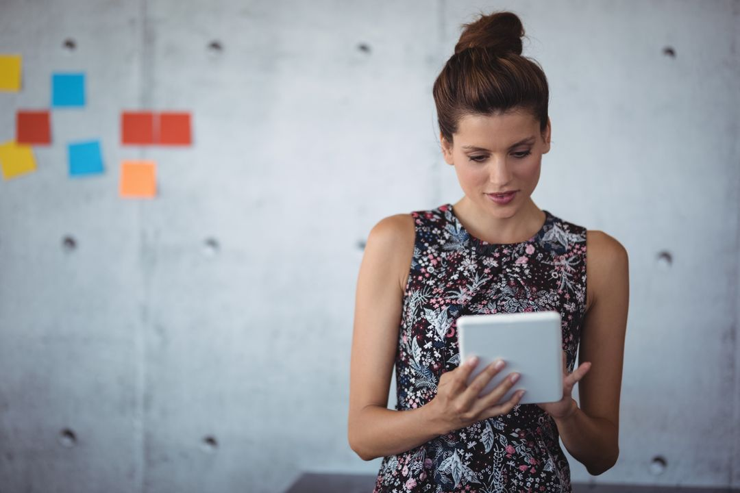 Young businesswoman using digital tablet while standing at creative office Free Stock Images from PikWizard