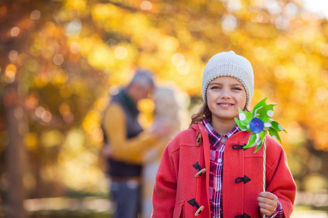 Portrait of smiling girl holding pinwheel toy at park during autumn Free Stock Images from PikWizard