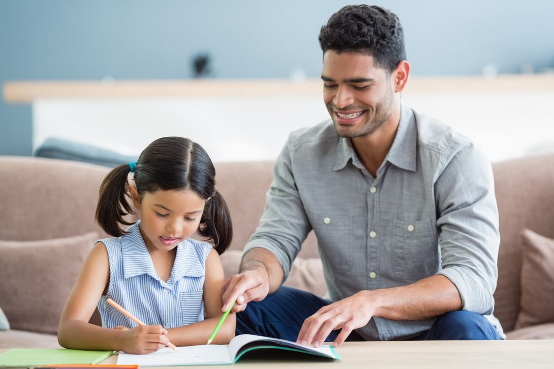 Father assisting her daughter in doing her homework at home