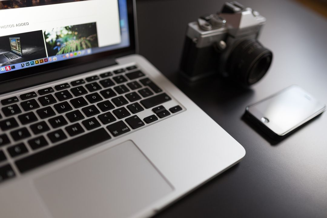 Image of a Laptop, a Camera and a Smartphone on a Desk
